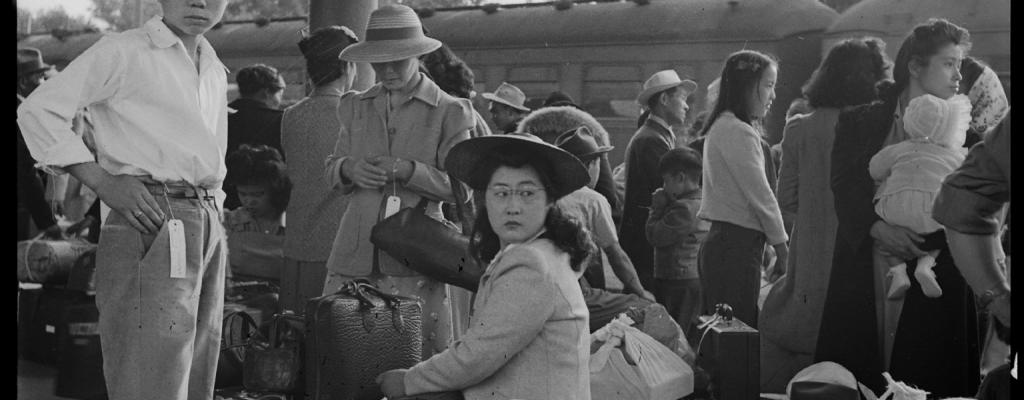Families of Japanese ancestry with their baggage at railroad station awaiting forced incarceration during WWII