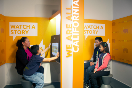"Visitors recording their own California immigration stories in an adjoining kiosk in ""We Are All Californians: Stories of Modern Immigration"" at the California Museum. Courtesy of West Office Exhibit Design."