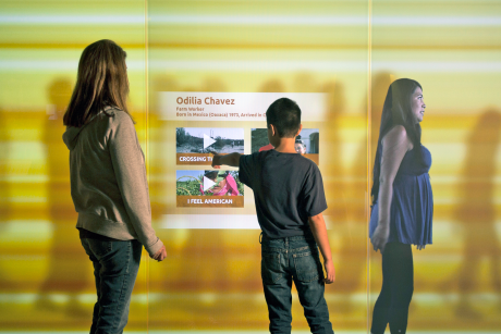 "Visitors interact with a 20' multimedia wall in ""We Are All Californians: Stories of Modern Immigration"" at the California Museum. Courtesy of West Office Exhibit Design."