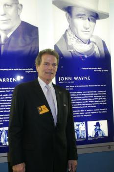Patrick Wayne in front of father John Wayne's CAHoF lobby panel