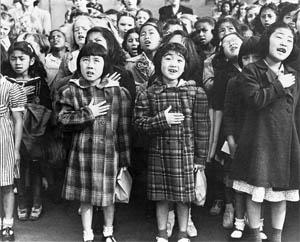 A historic photograph of Helene Nakamoto (left) and Mary Ann Yahiro (right) reciting the Pledge of Allegiance at their San Francisco elementary school before their relocation to the Topaz Internment Camp taken in 1942 by Dorothea Lange. PHOTO COURTESY OF NATIONAL ARCHIVES AND RECORDS ADMINISTRATION