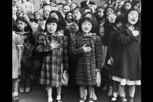 A historic photograph of Helene Nakamoto (left) and Mary Ann Yahiro reciting the Pledge of Allegiance at their San Francisco elementary school before their relocation to the Topaz Internment Camp. The photo was taken in 1942 by Dorothea Lange, National Archives and Records Administration