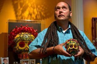 Artist Rob-O holds one of his sugar skull art pieces now on exhibit at the California Museum. He worked with a Sacramento business incubator known as Flywheel that works to give artists a boost. (Photo by Hector Amezcua / hamezcua@sacbee.com)
